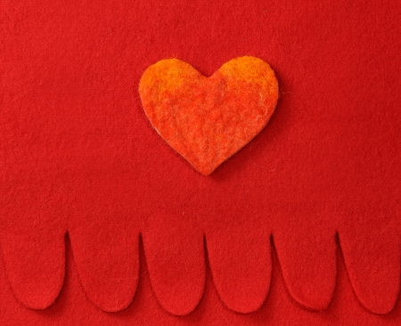 Felt heart on red background photo