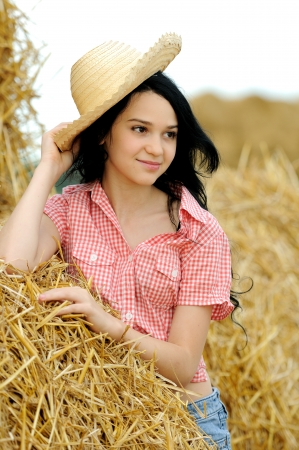 Beautiful girl enjoying the nature in the hay Фото со стока