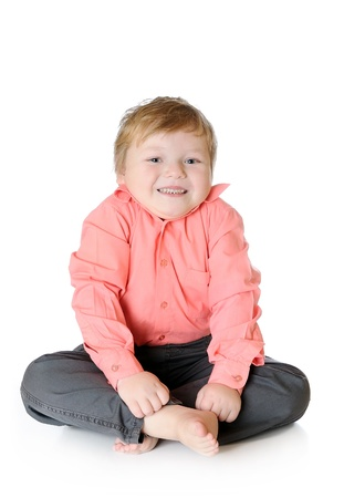 Adorable little boy smiling, sitting on the floor, studio shot, isolated on white background Stock Photo