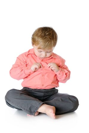 Adorable little boy sitting on the floor and looking to a button on a shirt