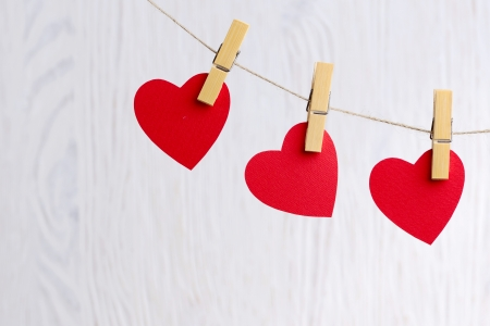 Three love hearts hanging on wooden texture background, valentines day card concept