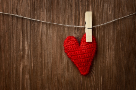 Love heart hanging on wooden texture background, valentines day card concept photo