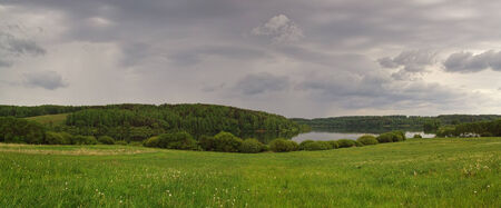 Panorama of the beautiful landscape with lake and meadow