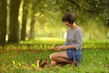 Young woman feeding squirrel with hazelnut in the park Stock Photo