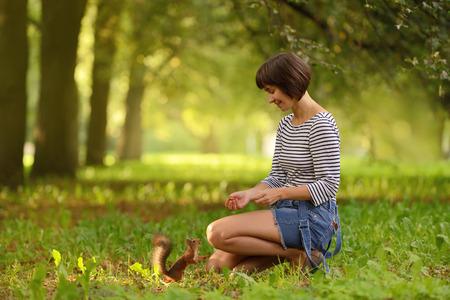 Young woman feeding squirrel with hazelnut in the park Zdjęcie Seryjne