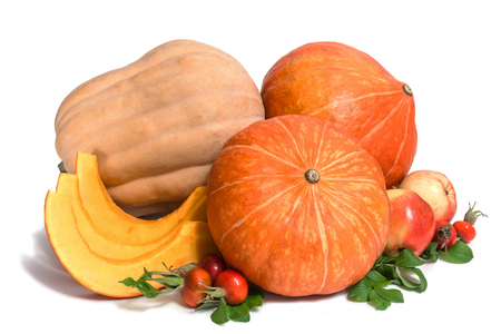 Two orange and one yellow pumpkins with three slices , two apples and rosehips with leaves isolated on white