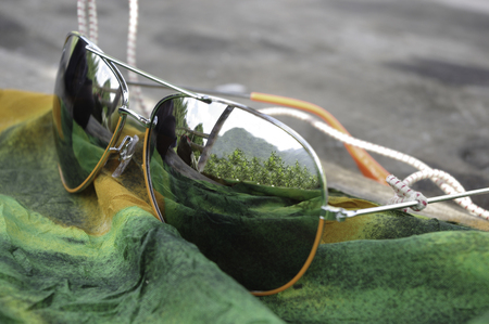 Mirrored sunglasses on green fabric
