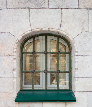 iron barred: Historic green window on the yellow wall in the daytime Stock Photo