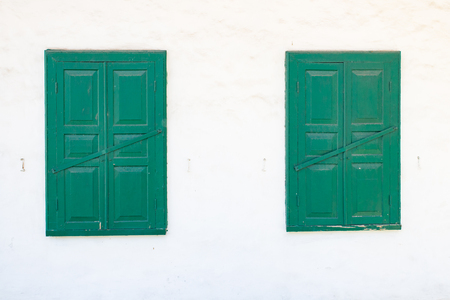 Two green windows on a white wall in the daytime