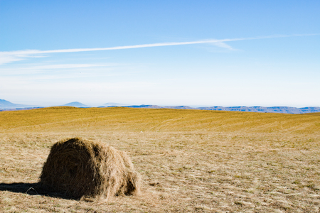 Haystack in autumn field, mountains in daytime