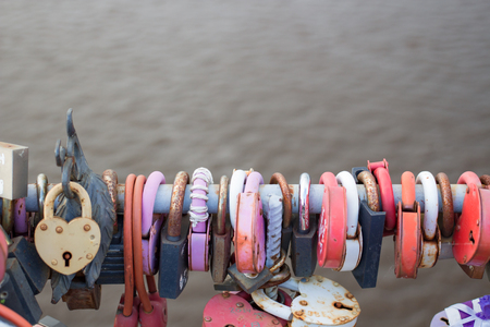 Many locks hang on the background of gray water Stock Photo