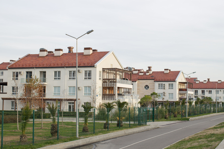 Pretty newly built homes and gardens near the road in the day time