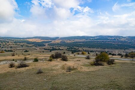 Panorama in autumn field, mountains in daytime Imagens