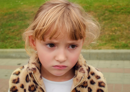 Portrait of a beautiful frowned little girl, close-up