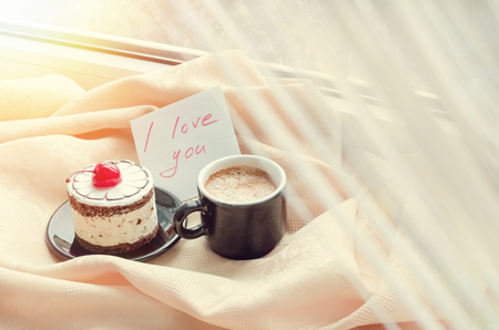 valentine day cup of coffee: Note I love you with cup of coffee and cake near the window and snow outside. Cozy winter breakfast. Good morning. Happy valentines day. Be my Valentine Note. Breakfast for a loved one.