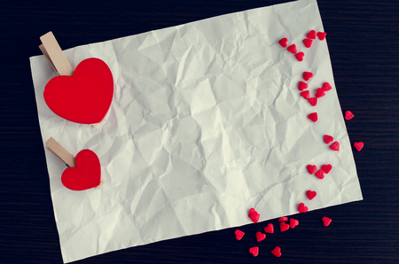creasy: Two red hearts and many small hearts with a piece of creasy paper on the dark wooden background. Empty space for text or photo. Picture frame. Valentines Day background. Valentines Day theme.