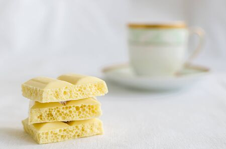 aerated: Heap of aerated porous white chocolate bars with cup of coffee on a white background. Stock Photo