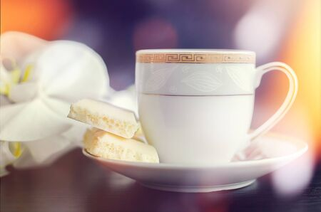 aerated: Piece of aerated porous white chocolate and cup of coffee on a dark background with white orchid.