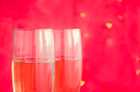 background couple: Valentines day background with two glasses of champagne on red background with bokeh in heart form. Stock Photo