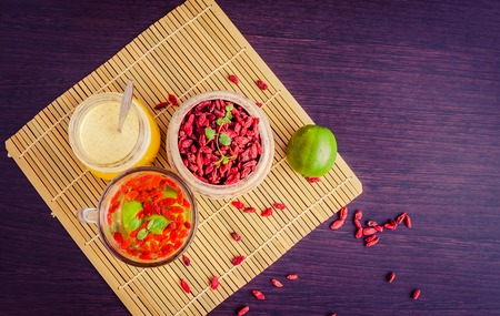 wolfberry: Cup of delicious dietary Goji berry tea with lime and honey on wooden background with measuring tape. Wolfberry for a healthy diet. Alternative medicine. Recovery. Rejuvenation. Slimming. Top view.