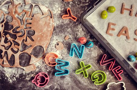 baking: Easter baking concept: raw dough for biscuit, colorful eggs, flour, cutters in the shape of letters on a dark wooden table. Easter baking preparation. Happy Easter. Top view.