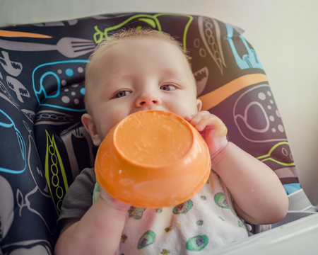 solid food: Baby eating in high chair from the plate, holding it in the hands. Baby boy feeding himself with messy face. Child having breakfast, making mess. Baby at meal time. Babys first solid food. Baby food.