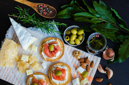 spoon: Delicious bruschetta with prosciutto and olives with cheese Parmesan and Bree on background of olive oil with spices, rosemary, garlic, Bay leaf, nuts and wooden spoon with pepper. Top view.