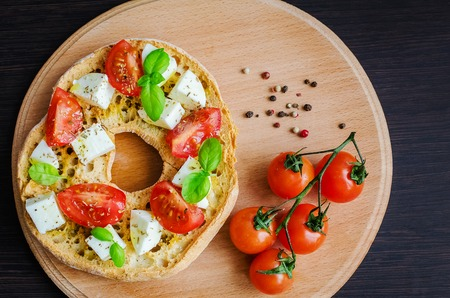 quick snack: Italian appetizer Friselle. Italian dried bread Friselle on wooden board with tomatoes cherry, basil and pepper. Italian food. Healthy vegetarian food. A quick and easy snack. Antipasti concept. Stock Photo