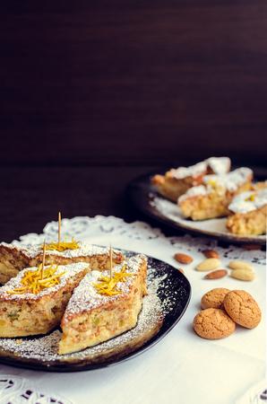 amaretto: Torta di riso - classical Italian dessert. Rice cake with almonds, candied orange peels and amaretto. A slices of rice cake with almond cookies in a plate. Italian food. Selective focus. Stock Photo
