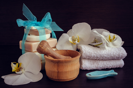 pounder: Composition of spa treatment on dark wooden background. Spa and wellness setting in white ans blue colors with natural homemade soaps, wooden pounder, flowers and soft towels. Selective focus. Stock Photo