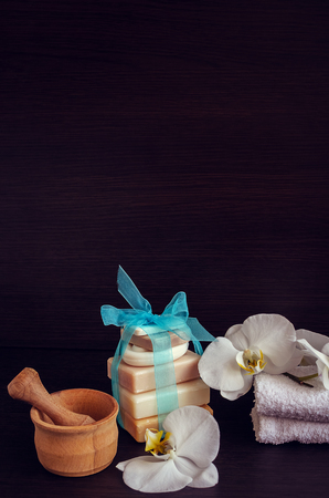 pounder: Spa and wellness setting with natural soap, flowers, wooden pounder and towels. Spa still life in white and blue colors on dark wooden background with place for text. Selective focus. Copy space.
