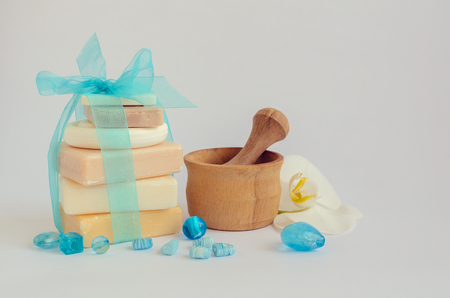 pounder: Spa setting in pastel and blue colors with different kind of natural soaps, orchid and the wooden pounder on white background. Tower stack of different handmade soaps on white. Selective focus. Stock Photo