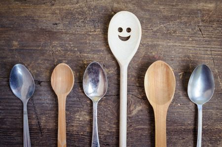 dissent: One spoon with smiley face standing out from the crowd - individuality. Leadership, uniqueness, independence, initiative, dissent, think different, success, happyness, smile, positivity concept.