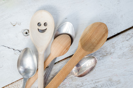 happyness: One spoon with smiley face standing with the crowd - individuality. Leadership, uniqueness, independence, initiative, dissent, think different, success, happyness, smile, positivity concept. Stock Photo