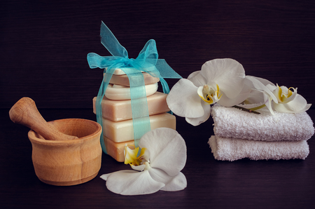 pounder: Spa and wellness setting with natural soap, flowers, wooden pounder and towels. Spa still life in white and blue colors on dark wooden background. Selective focus.