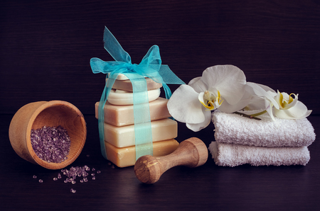 pounder: Spa setting in purple and blue colors with different kind of natural soaps, orchid and the wooden pounder on dark wooden background. Tower stack of different handmade soaps. Selective focus.