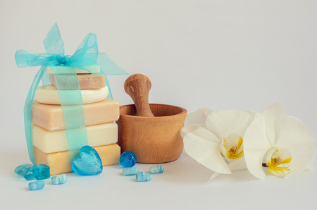 pounder: Spa setting in pastel and blue colors with different kind of natural handmade soaps, orchid and the wooden pounder on white background. Selective focus. Copy space.