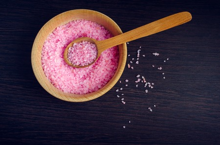Spa and wellness concept - pink sea salt in the bowl with the wooden spoon on dark wooden background. Aromatherapy concept. Top view. Copy space.