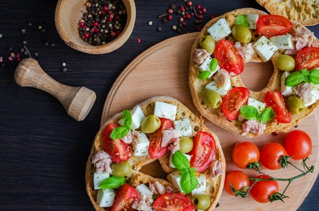 pounder: Italian appetizer Friselle. Italian dried bread Friselle with tomatoes cherry, cheese mozzarella, olives, tuna, basil and pepper in wooden pounder. Italian food. Healthy vegetarian food. Top view.