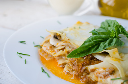 Close-up of a traditional lasagna made with minced beef bolognese sauce and bechamel sauce topped with basil. Portion of tasty homemade lasagna on wooden table. Italian food concept. Selective focus. Stock Photo