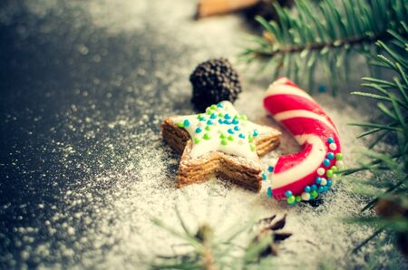christmastime: Christmas gingerbread cookies, candy and fir tree on chalkboard background with space for text. Merry Christmas and Happy New Year. Xmas concept. Selective focus.. Copy space. Stock Photo
