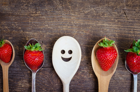 dissent: Strawberries on spoons and wooden spoon with smiley face. Leadership, uniqueness, independence, initiative, strategy, dissent, think different, success, summer, happiness, smile, positivity concept. Stock Photo