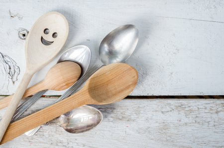 dissent: One spoon with smiley face standing with the crowd - individuality. Leadership, uniqueness, independence, initiative, dissent, think different, success, happiness, smile, positivity concept. Stock Photo