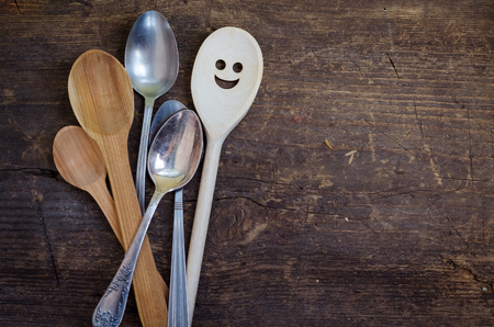 the distinguished: One spoon with smiley face standing with the crowd - individuality. Leadership, uniqueness, independence, initiative, dissent, think different, success, happyness, smile, positivity concept. Stock Photo
