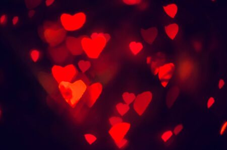 black magic: Red hearts bokeh in dark texture for use in graphic design. Valentines style defocused lights background. St. Valentines Day. Stock Photo
