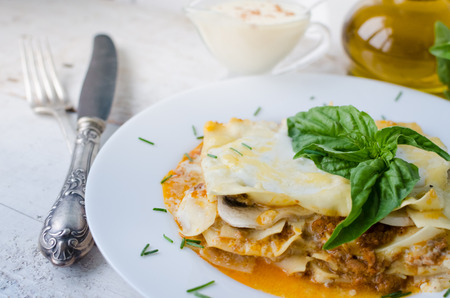 Traditional lasagna made with minced beef bolognese sauce and bechamel sauce topped with basil leaves. Portion of tasty homemade lasagna on white wooden table. Italian food concept. Selective focus.