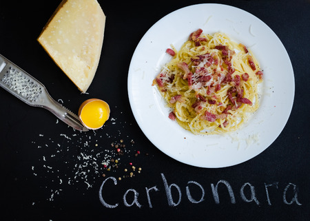 Pasta Carbonara. Spaghetti with bacon and parmesan cheese. Pasta Carbonara on white plate with parmesan on dark background with word Carbonara. Italian food concept. Top view.