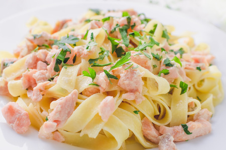 Italian Wholemeal Pasta Tagliatelle with Salmon and Parsley. Close up Fresh pasta with smoked salmon in the sauce on white wooden background. Italian cuisine concept. Selective focus. Stock Photo
