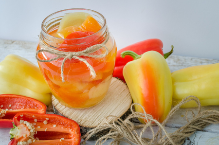 Bell pepper preserved in a glass jar with fresh peppers on white wooden background. Homemade marinated in oil red pepper. Glass jar with conserved roasted sweet paprika. Selective focus. Banco de Imagens