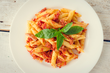speciality: Italian Wholemeal Pasta Penne with Tuna and Basil. Fresh pasta with tuna and tomato sauce on white wooden background. Baked penne pasta with tuna fish and tomato sauce. Italian food concept. Top view.